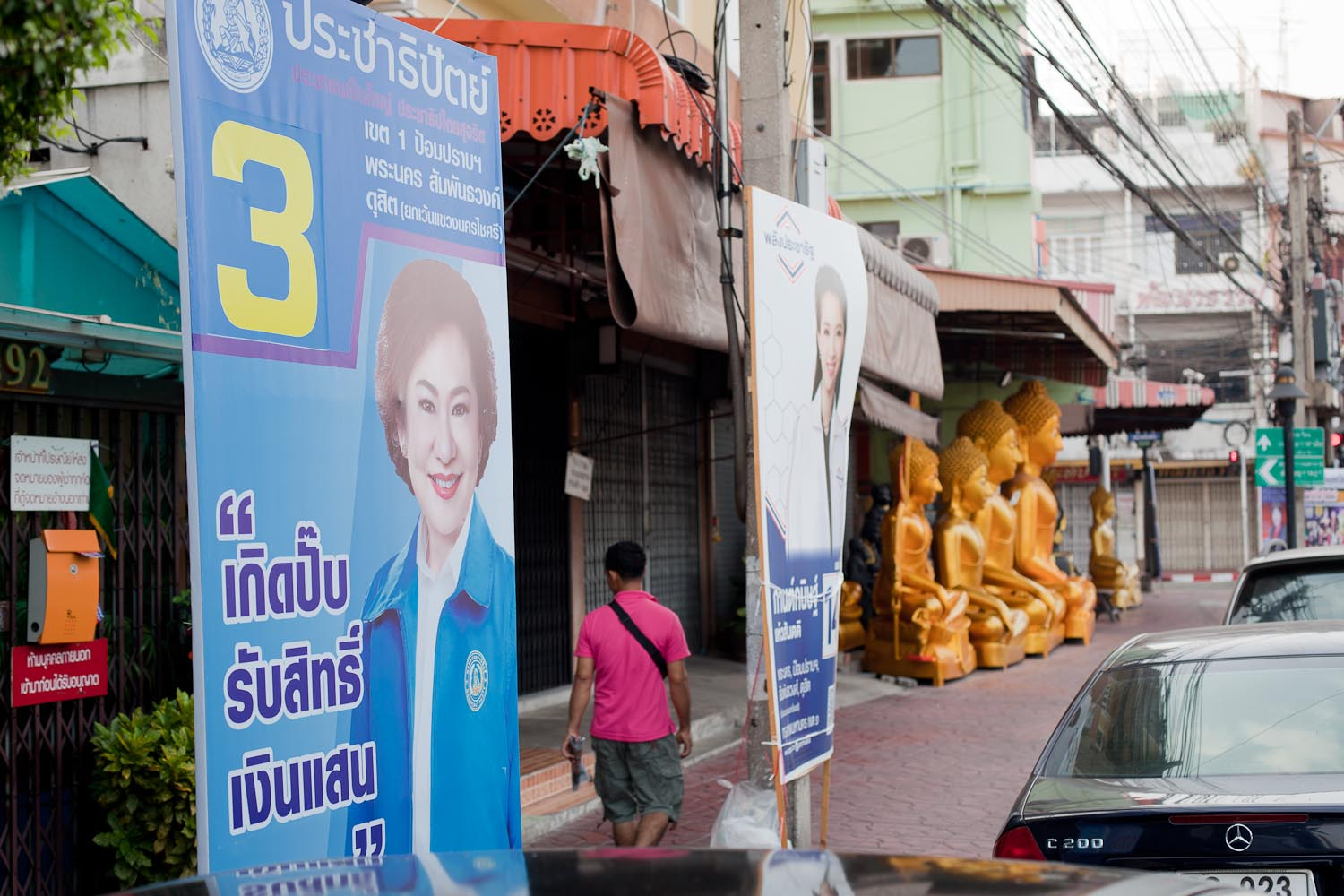 "Phak Prachathipat (Democrat Party): ""Entitlement to receive 100,000 Baht by birth."" In the background: Phak Phalang Pracharat (People's State Power Party)"