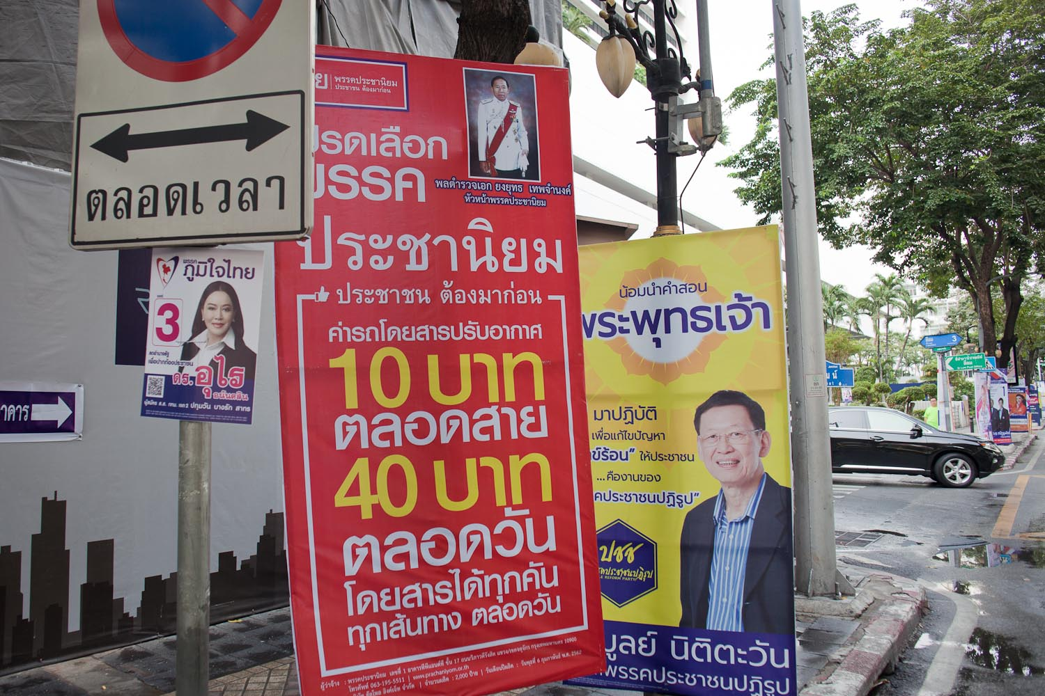 "Phak Prachaniyom (Populist Party): ""People are the priority. Air-conditioned buses for 10 Baht along the whole line, 40 Baht for the whole day of transportation on all lines.""  In the background: Phak Phumjai Thai (Proud to Be Thai Party); Phak Prachachon Patirub (People Reform Party)"