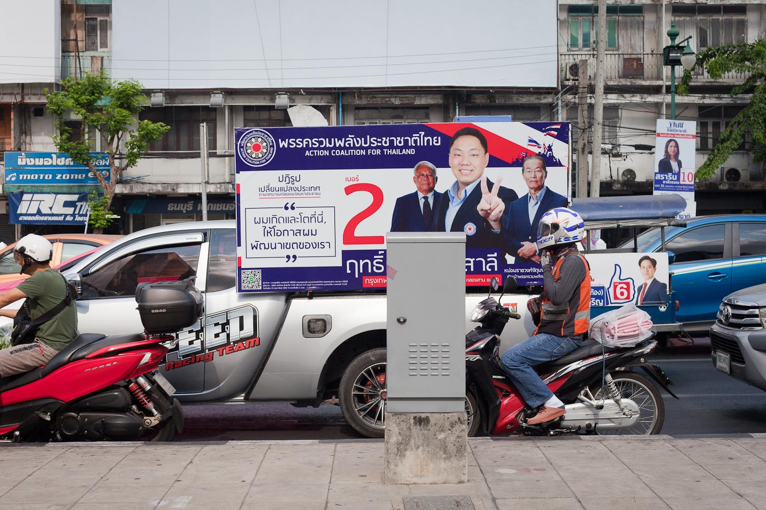 "Campaign pick-up of Phak Ruam Phalang Prachachart Thai (Action Coalition for Thailand): ""Reform. Change the country according to the intention of the people. – I was born and grew up here. Give me the chance to develop our district.""  In the background: Phak Thai Raksa Chart (Thai Save the Nation Party)"